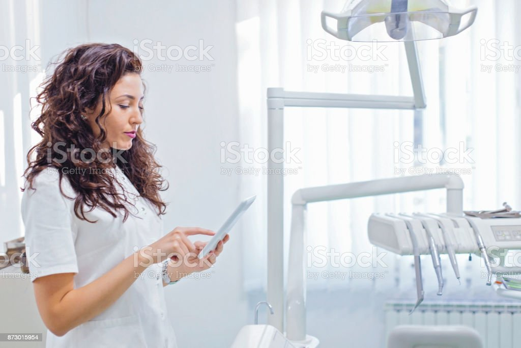 Young dentist standing in office and using digital tablet stock photo