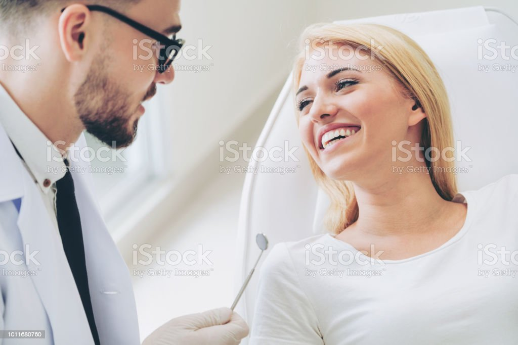 Junger Zahnarzt spricht mit Patienten in Zahnklinik. – Foto