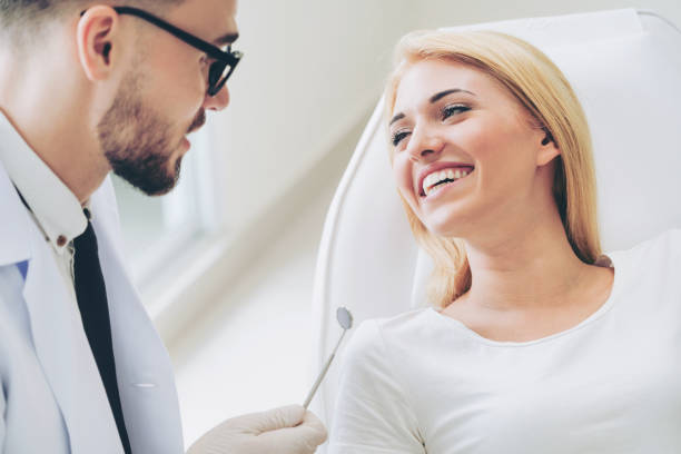 Young dentist talks with patient in dental clinic. Young handsome dentist talks with happy woman patient sitting on dentist chair in dental clinic. Dentistry care concept. implant stock pictures, royalty-free photos & images