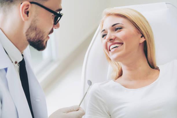 young dentist talks with patient in dental clinic. - dentista foto e immagini stock