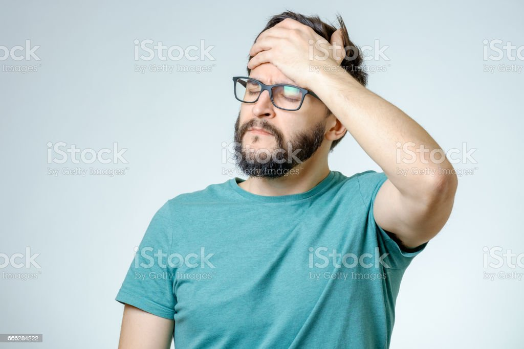 Young depressed handsome bearded man touching his head and having a headache over gray background stock photo