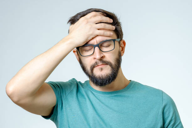 young depressed handsome bearded man touching his head and having a headache over gray background - frowning stock photos and pictures