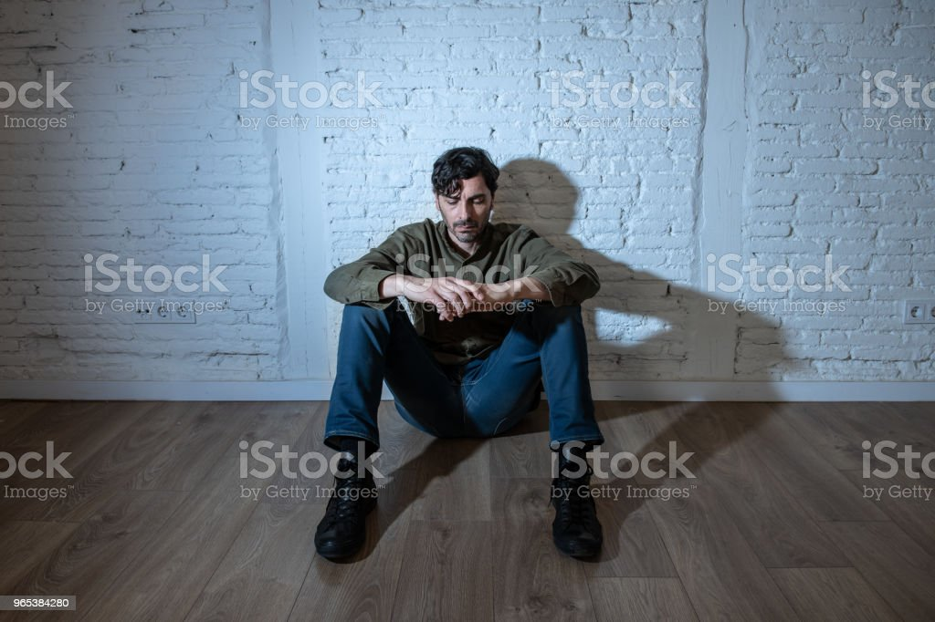 young depressed man sitting against a white wall at home with a shadow on the wall feeling miserable, lonely and sad in mental health depression concept royalty-free stock photo