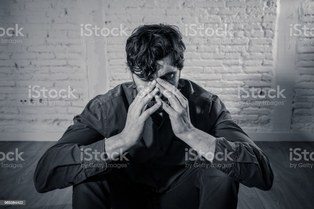 young depressed man sitting against a white wall at home with a shadow on the wall feeling miserable, lonely and sad in mental health depression concept zbiór zdjęć royalty-free