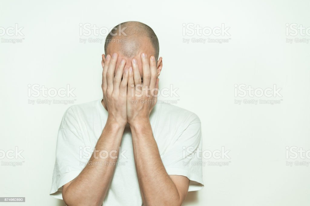 Young depressed man suffering from anxiety and feeling miserable cover his face with his hands and leaning on the white wall isolated stock photo