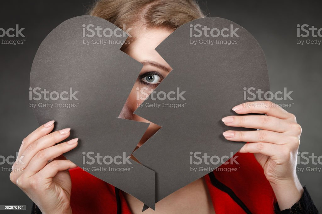 Young depressed woman covered by broken heart. stock photo