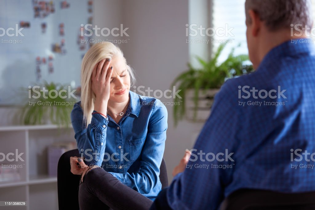 Young depressed woman discussing with therapist Depressed female student discussing with therapist. Mature social worker advising young woman in meeting. They are sitting at lecture hall in university. 18-19 Years Stock Photo