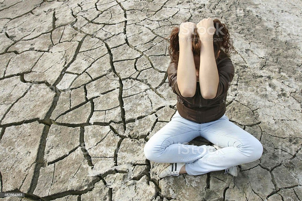 Young depressed woman sitting in the middle of empty desert. stock photo