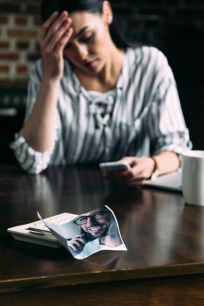 jeune femme déprimée à l'aide de smartphone avec photo froissé d'ex-petit ami sur le premier plan - Photo
