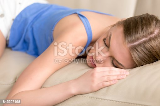 istock Young deprived sleeping woman lying asleep on sofa, close up 845527198