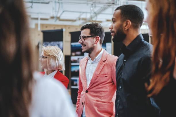 jóvenes profesionales hablando en la oficina de diseño - art gallery fotografías e imágenes de stock