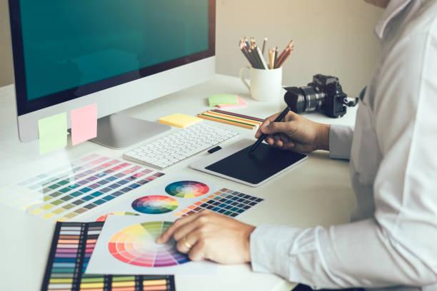 会社のオフィスに座って、デジタル グラフィック タブレットに取り組んでいる若手デザイナー。 - デザイン ストックフォトと画像