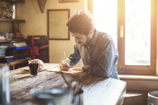 Young hipster man sketching on a  notebook on a rustic wooden table during his lunch break