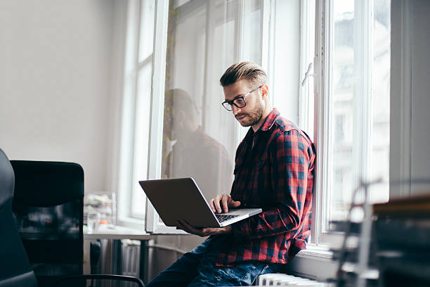 Young designer working from home office Young man working on laptop by the home office window plaid shirt stock pictures, royalty-free photos & images