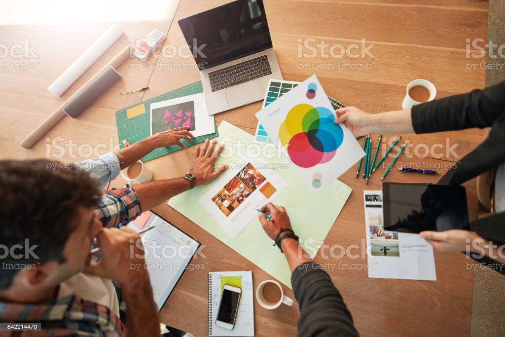 Young designers discussing the color palette Top view shot of young designers discussing the color palette. Creative team brainstorming around table working together on new project. Adult Stock Photo