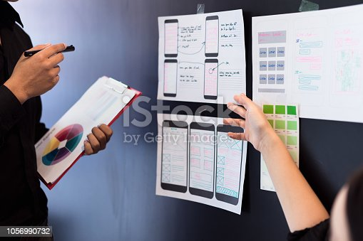 istock Young designers teamwork working with color samples mobile responsive website development with UI/UX, Brainstorming Planning. 1056990732