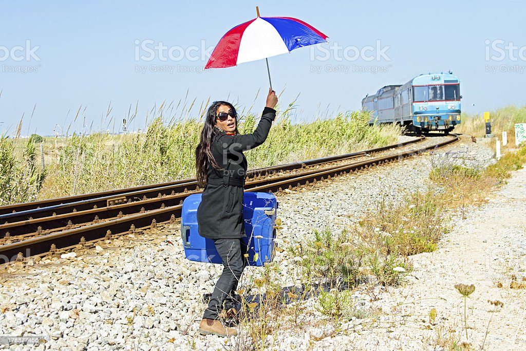 Young desperate woman at a passing train royalty-free stock photo