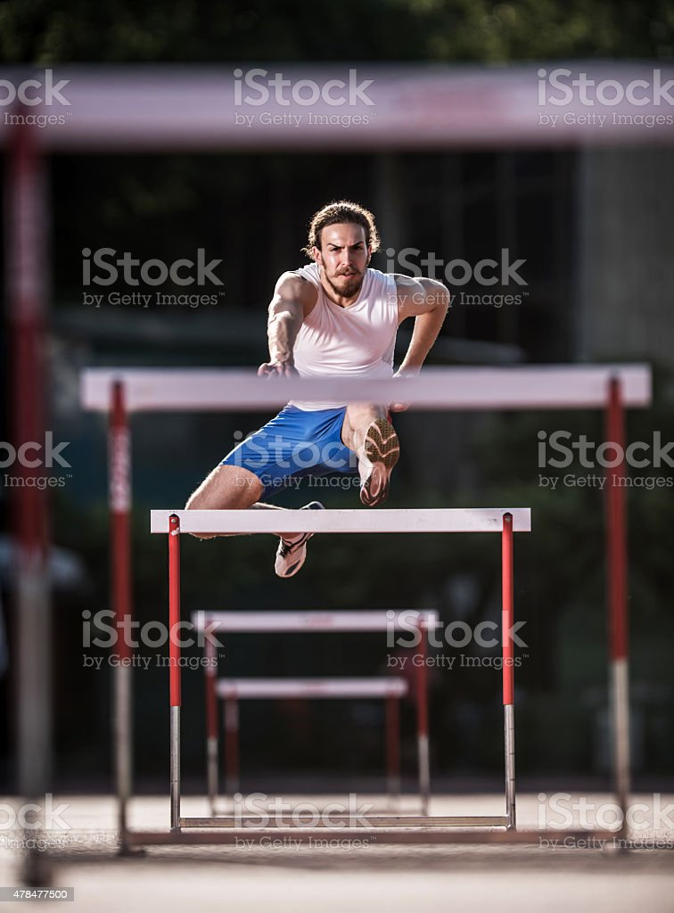 Young determined athlete jumping hurdles on a race. stock photo