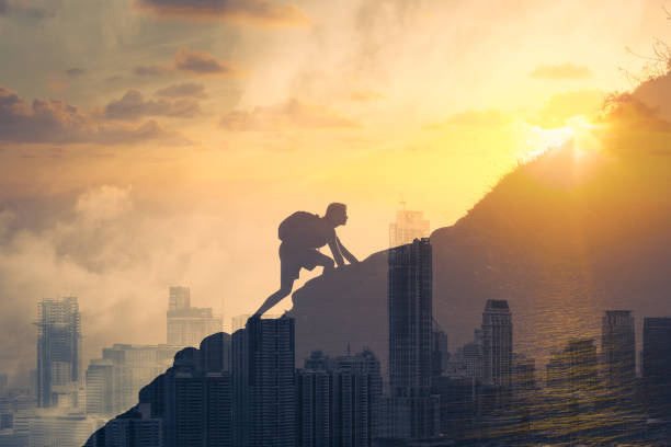 Young determined man climbing up mountain overlooking the city. stock photo