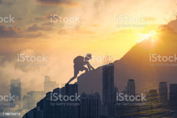 Photo of Young determined man climbing up mountain overlooking the city.