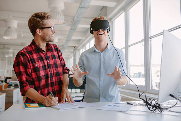 Young developers testing new virtual reality device stock photo