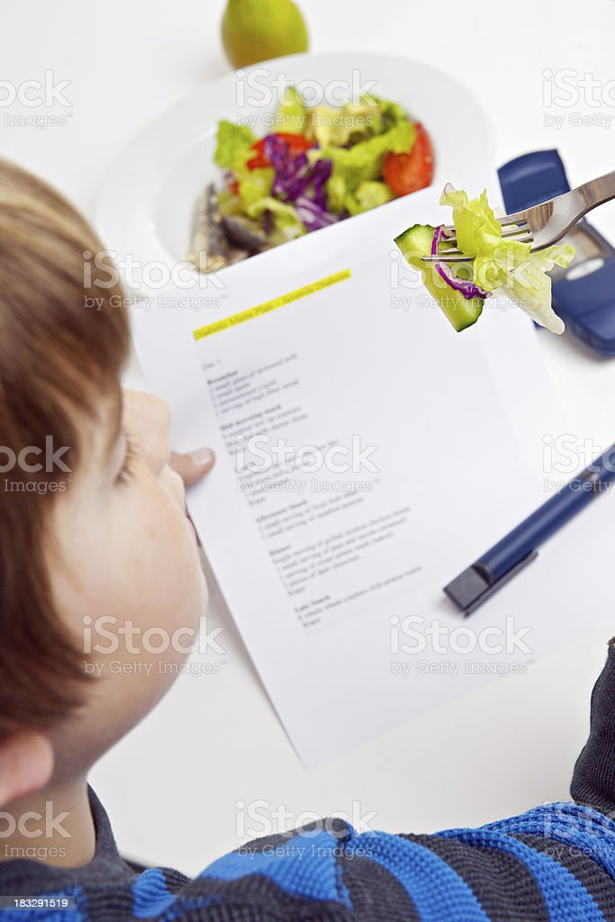 Young diabetic boy reading a menu plan at lunchtime stock photo