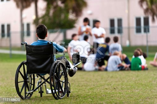 twelve years old child sitting in a wheel chair watching other kids getting together in the park while he is left behind