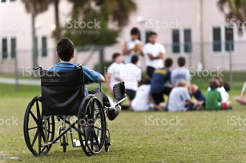 young disabled boy looking upon his peers leaving him out stock photo