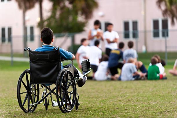 junge behinderte junge schaut auf seine kollegen, die ihn - vorurteil stock-fotos und bilder