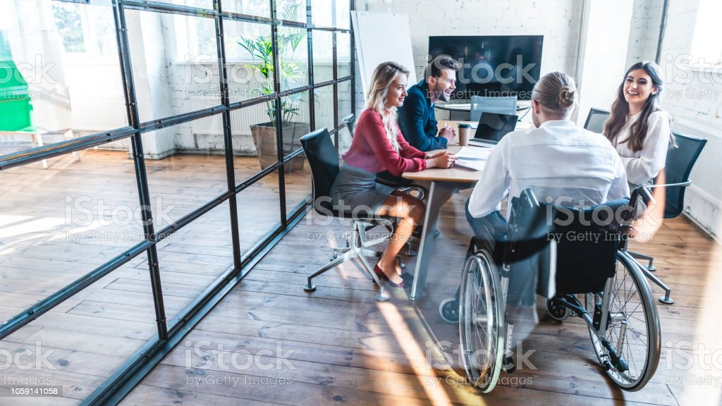 young disabled businessman in wheelchair working with smiling colleagues in office - Royalty-free Adulto Foto de stock
