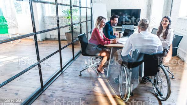 Young Disabled Businessman In Wheelchair Working With Smiling Colleagues In Office - Fotografias de stock e mais imagens de Adulto