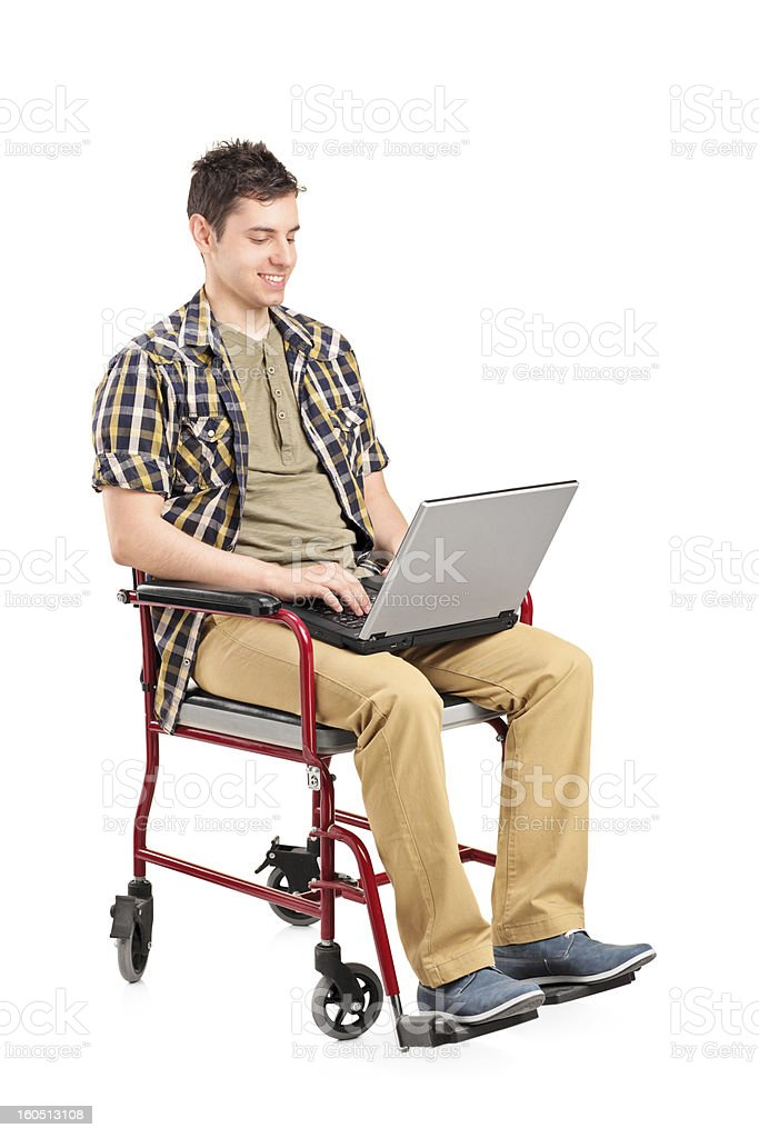 Young disabled man in a wheelchair working on laptop royalty-free stock photo