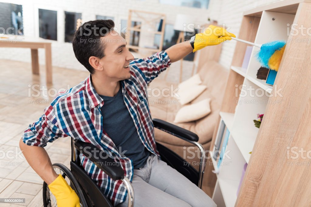 A young disabled man is cleaning himself at home. stock photo