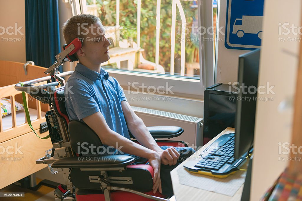 Young disabled man playing computer game stock photo