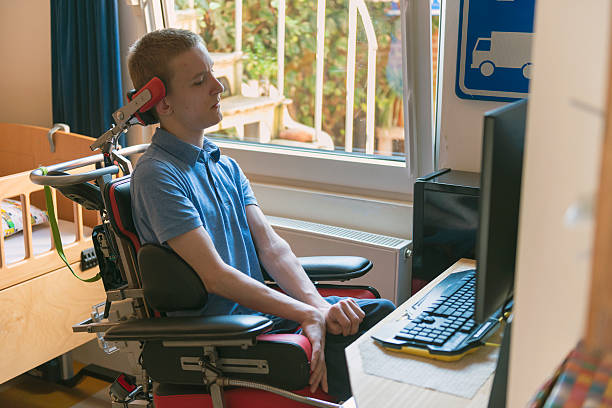 Young disabled man playing computer game Color image of a real life young physically impaired ALS patient computer gaming with the help of his electronic wheelchair. als stock pictures, royalty-free photos & images