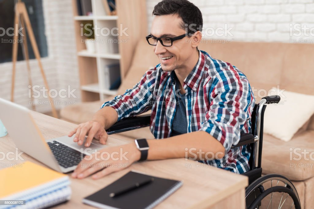 A young disabled man works at home. stock photo