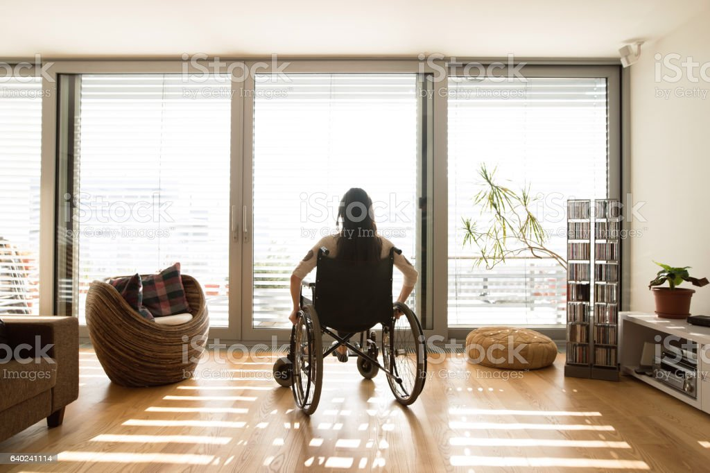 Young disabled woman in wheelchair at home, rear view. stock photo