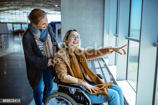 Young disabled woman on wheelchair and carer waiting at airport and looking at window view