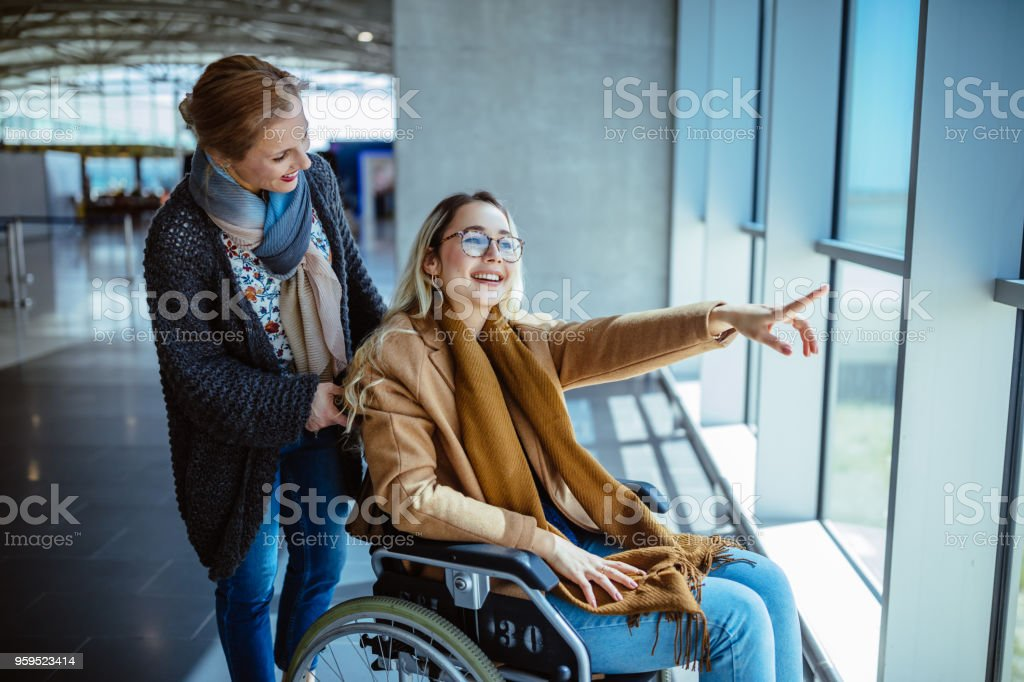 Young disabled woman on wheelchair and mother waiting at airport stock photo