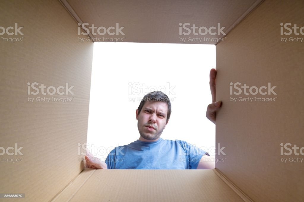 Young disappointed man is looking on gift inside cardboard box.