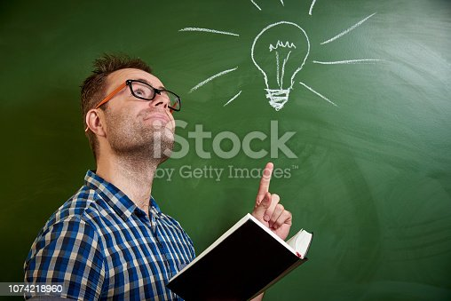 istock A young disheveled man with glasses is reading a book, an idea comes to mind on the background of a blackboard with a chalked light bulb. 1074218960