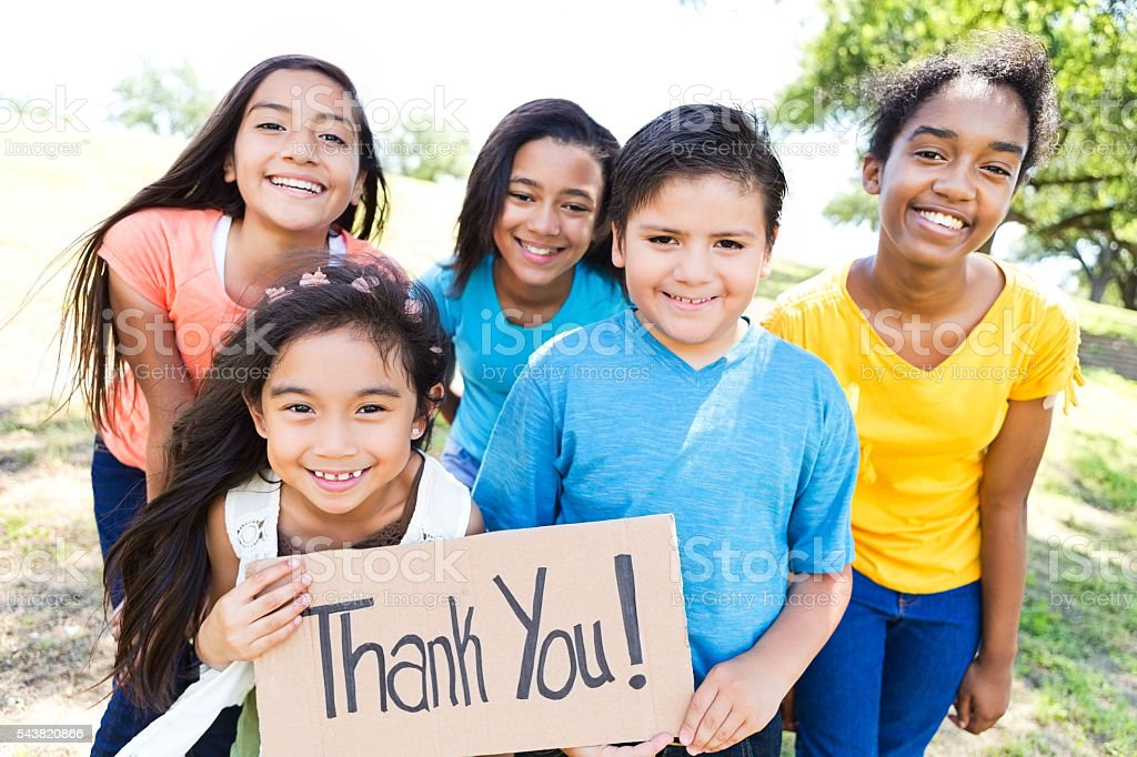 Young diverse friends in local park hold 'Thank You!' sign stock photo