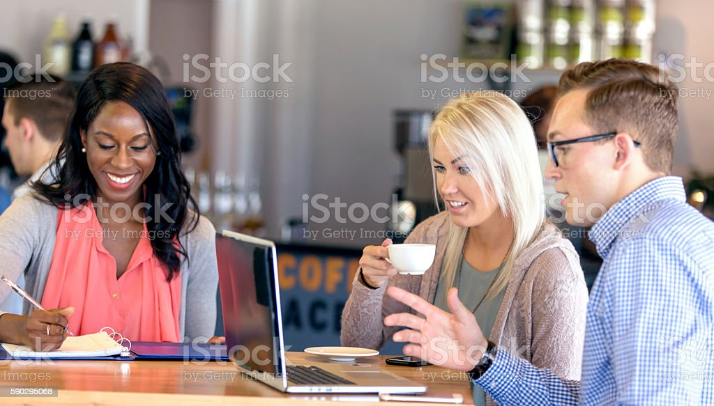 Young diverse group of friends enjoying a coffee shop meeting royaltyfri bildbanksbilder