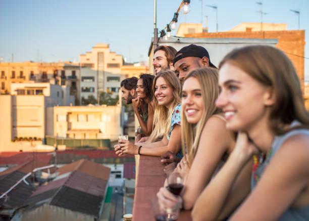 junge vielfältige gruppe von menschen auf dachterrasse beobachten sonnenuntergang - paletten terrasse stock-fotos und bilder