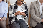 istock Young diverse people sitting in chair using smartphones 1063372434