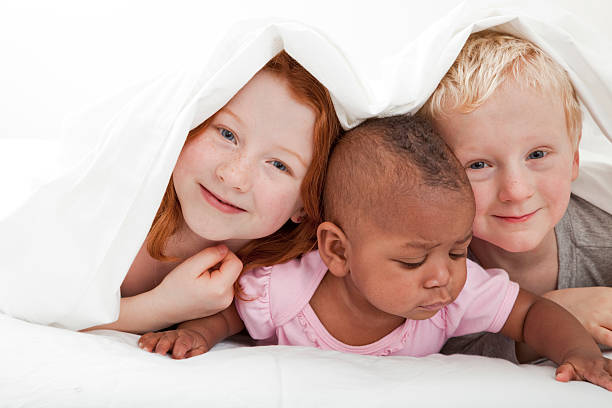 young diverse race children playing under the covers stock photo