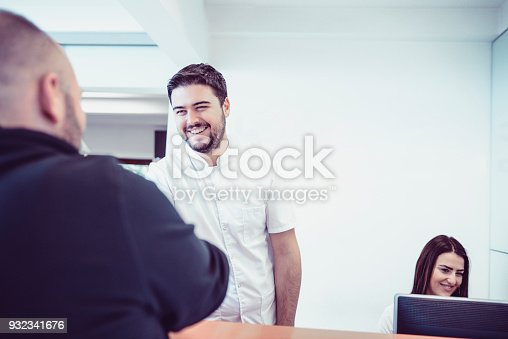 istock Young Doctor and His Assistant Make Appointment on Reception in Clinic 932341676