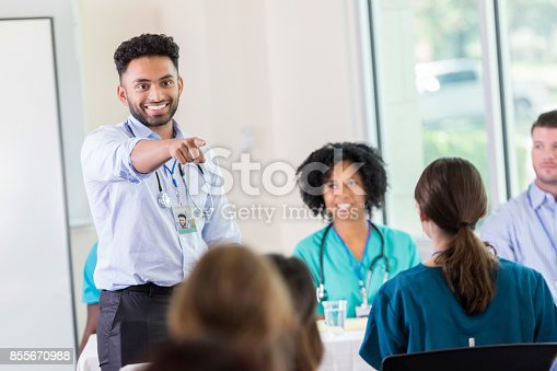 istock Young doctor calls on someone to answer  question during conference 855670988