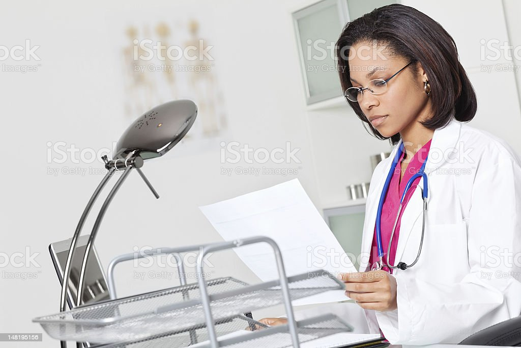 Young Doctor Concentrating on Her Work in Doctor's Office royalty-free stock photo
