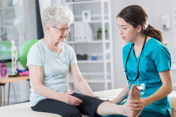joven médico examina la pierna del paciente mayor - enfermedades de los pies fotografías e imágenes de stock